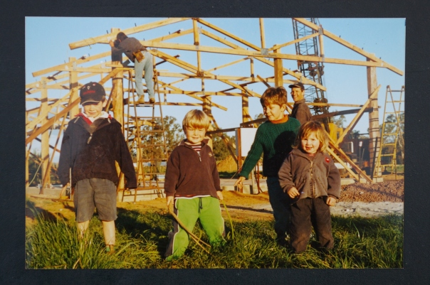 Farm building under construction, Aug 2003. Trevor Northey checking the frame with Bill Crocker's restored 1946 Blitz gantry crane placing the truss. Felix and Grace, with cousins Ned and Joey, are in the foreground, with David behind.